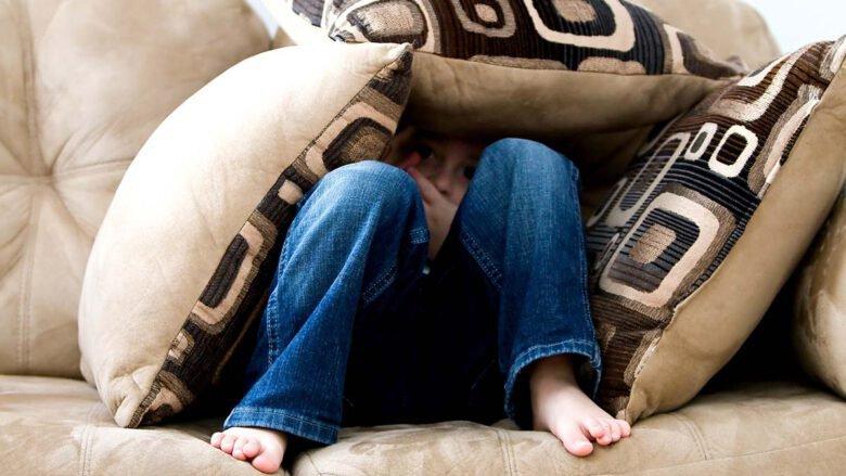 Junge versteckt sich unter Kissen